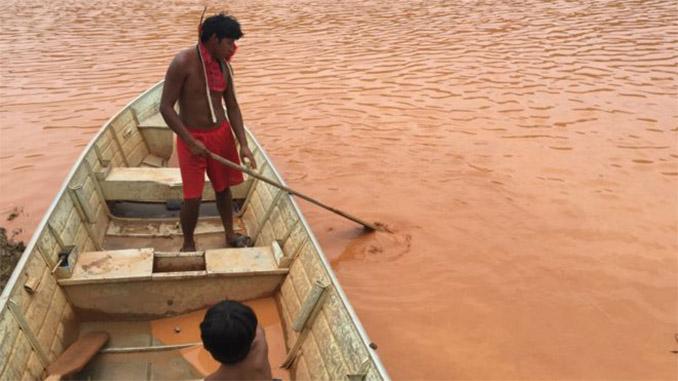 """""""Só sairemos quando tiverem a dignidade de conversar com a gente. Destruíram nossa vida, arrasaram nossa cultura, e nos ignoram. Não aceitamos"""", disse o índio Aiá Krenak. Ele mostra a consistência espessa da água à reportagem. Foto: BBC Brasil"""